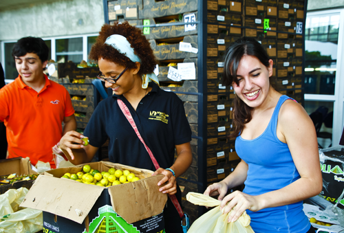 Student smiling and reaching a product at food pantry