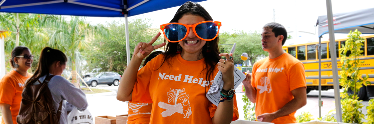 Volunteer at information booth wearing oversize sunglasses