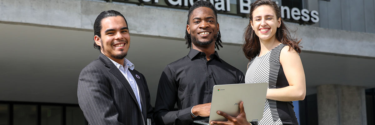 MDC students wearing business attire and holding a laptop