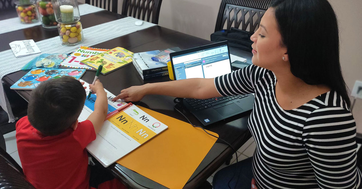 MDC alumna working from home with her son doing homework