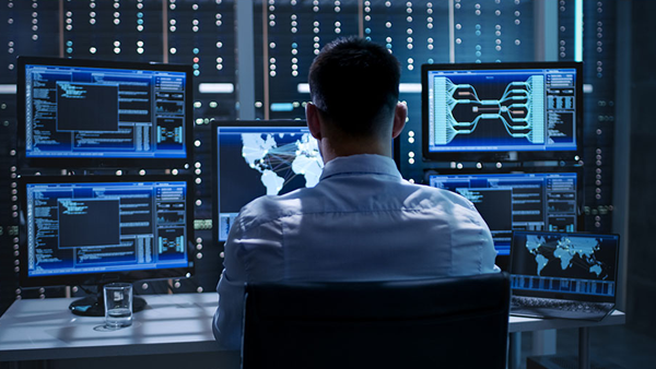 Person sitting in front of computer screens performing cybersecurity