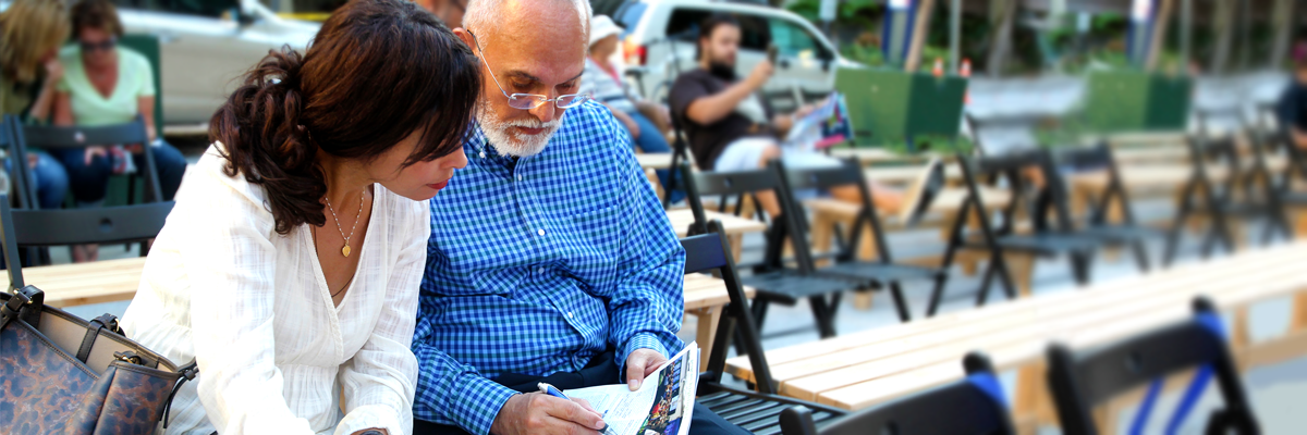 An elder man and woman sitting by bench planning