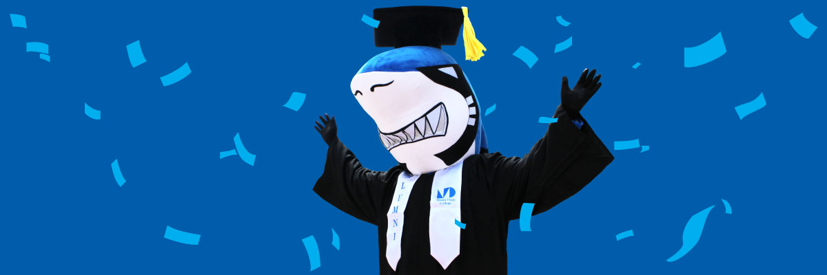Finn wearing cap and gown with alumni stole and confetti