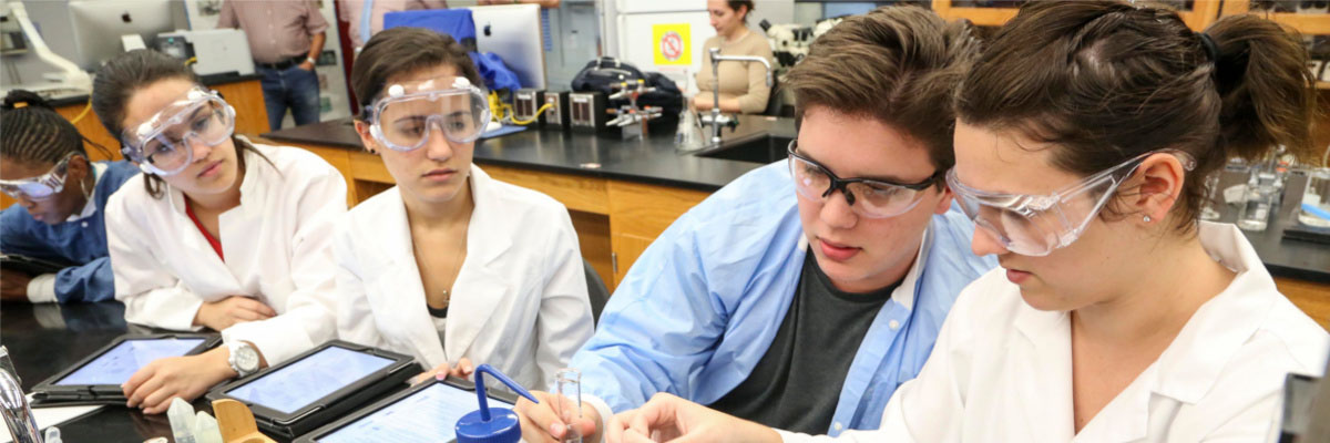 Students wearing goggles in science lab