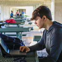Student outdoors with laptop computer