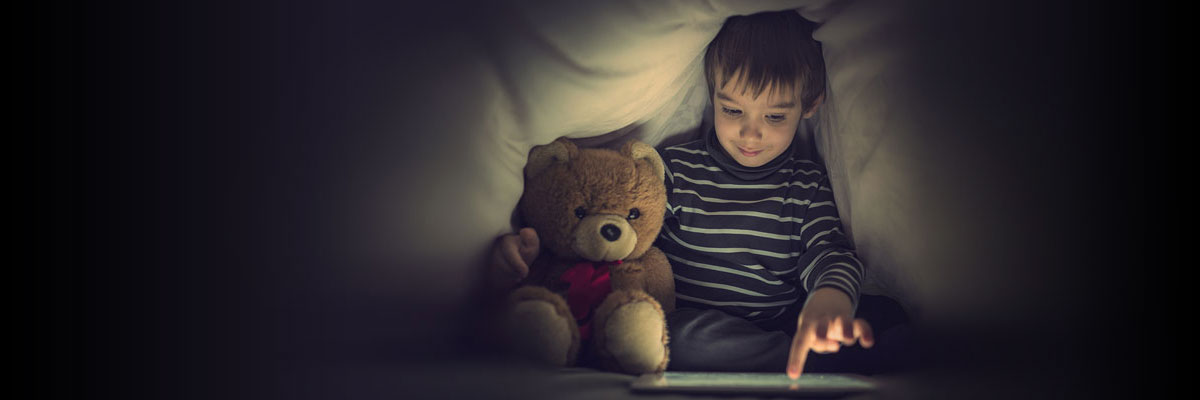 Child with plush bear viewing a tablet