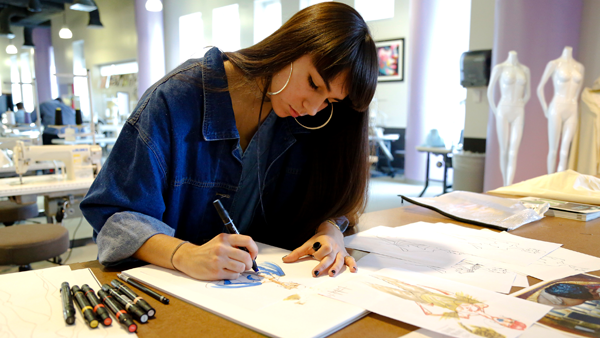 Student sketching designs at Miami Fashion Institute