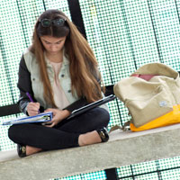 Student sitting on a bench studying
