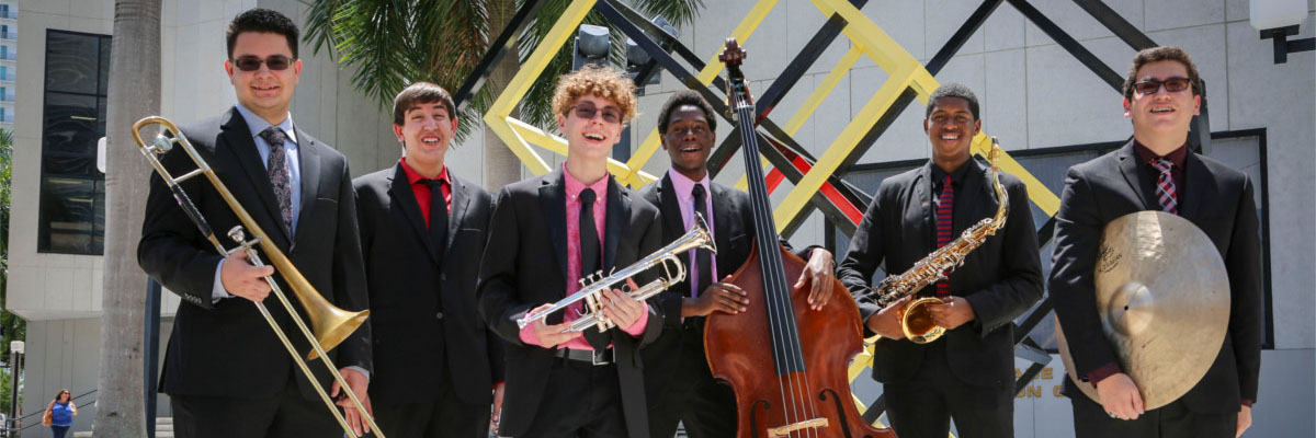 Group of student musicians smiling holding instruments at MDC Wolfson Campus